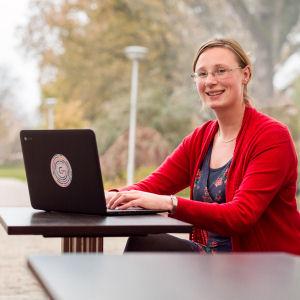 Vrouw aan tafel achter laptop