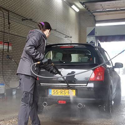 Vrouw spuit auto schoon