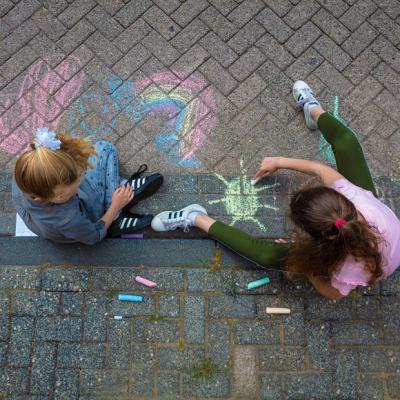 Twee kinderen aan het stoepkrijten