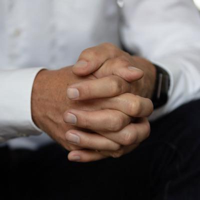 Man met handen in elkaar gevouwen.