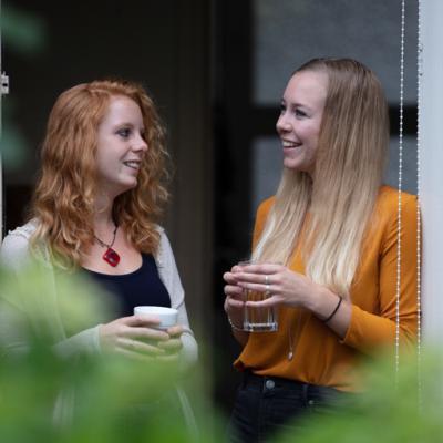 Twee meiden drinken thee in de deuropening