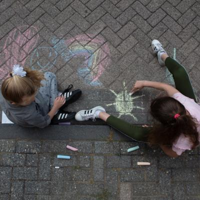 2 meisjes aan het stoepkrijten