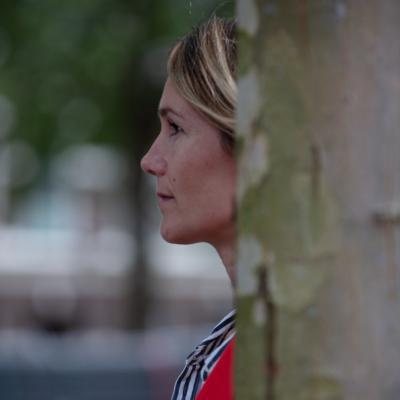 Vrouw achter een boom