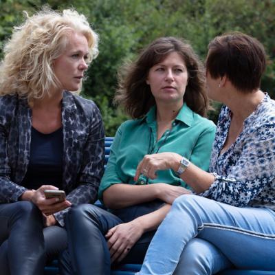 Drie vrouwen in gesprek op bankje
